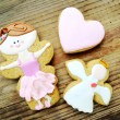 Gingerbread in a shape of heart and angel with pink and white icing and little cute ballet dancer on wooden table — Stock Photo #66002265