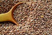 Buckwheat grains with an old big spoon on wooden table — Stockfoto