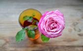 Sola rosa en un florero pequeño en la mesa de madera — Foto de Stock