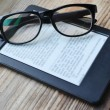 Black ereader with retro glasses on wooden table — Stock Photo #66436167