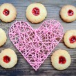 Romantic concept with handmade pink heart and lots of homemade cookies with jam on wooden table — Stock Photo #66665659