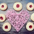 Romantic concept with handmade pink heart and lots of homemade cookies with jam on wooden table — Stock Photo #66665663