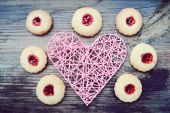 Romantic concept with handmade pink heart and lots of homemade cookies with jam on wooden table — Stock Photo