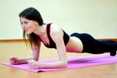 Young active woman doing plank exercise in a gym — Stock Photo