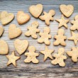 Gingerbread cookies in shapes of heart, star and man on wooden table — Stock Photo #67514563