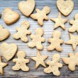 Gingerbread cookies in shapes of heart, star and man on wooden table — Stock Photo #67514595