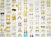 Set of different small earrings against white background — Stock Photo
