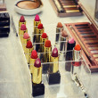 Set of colorful lipsticks with other cosmetics on a dressing table — Stock Photo #69127769