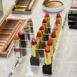 Set of colorful lipsticks with other cosmetics on a dressing table — Stock Photo #69127801