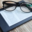 Black ereader with retro glasses on wooden table — Stock Photo #69149711