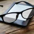 Black ereader with retro glasses on wooden table — Stock Photo #69149749