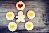 Homemade cookies in shape of man and with heart shaped jam on wooden table — Foto de Stock