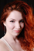 Beautiful young redhead woman with perfect daytime makeup and long silver earrings smiling playfully — Stock Photo