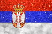 The National flag of Serbia made of bright and abstract blurred backgrounds with shimmering glitter — Stock Photo