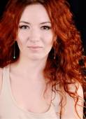 Beautiful young redhead woman with perfect daytime makeup and long silver earrings smiling — Stock Photo