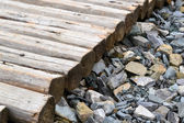 Lots of little gray pebble stones with a pile of firewood logs and blocks — Stock Photo