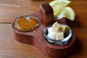 A set of tea toppings and sweeteners: a bit of honey, brown and white sugar, and a lemon — Stock Photo