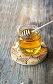 Golden honey with honeystick. cinnamon and anise stars on wooden table — Stock Photo