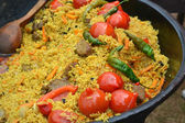 Large pot with Uzbek pilaf with tomatoes and green chilli peppers — Stock Photo