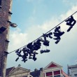 Filtered Picutre of Shoes Hanging from Wire — Stock Photo #57025635