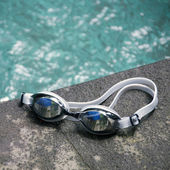 Swimming sport goggles on the poolside — Stock Photo
