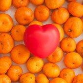 Plastic heart and mandarines — Stock Photo