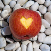 Apple with a cut heart symbol — Stock Photo