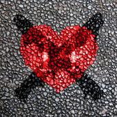 Red heart symbol on the grainy asphalt texture — Stock Photo