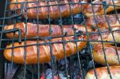Barbecue with fiery sausages on the grill — Stock Photo
