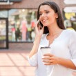 Woman holding coffee cup and talking on phone — Stock Photo #51932325