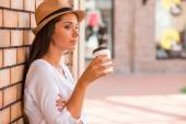 Woman in funky hat holding cup with hot drink — Stock Photo