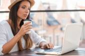 Woman working on laptop and drinking coffee — Stock Photo