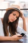 Deprimerad kvinna som tittar på mobiltelefon — Stockfoto