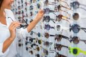 Woman choosing sunglasses in store — Stock Photo