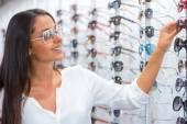 Woman choosing sunglasses in optic store — Stock Photo