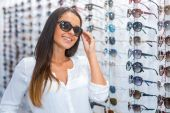 Woman adjusting sunglasses in optic store — Stock Photo