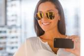 Woman making selfie in optic store — Stock Photo