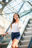 Woman talking on mobile phone and moving by escalator — Stockfoto