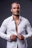 Black man dressing up his shirt — Stock Photo