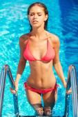 Woman in bikini getting out from the pool — Stock Photo