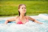 Woman in bikini relaxing in hot tub — Stock Photo