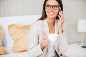 Businesswoman  drinking coffee and talking on mobile phone — Stock Photo