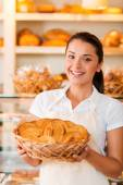 Woman in apron holding basket with baked goods — Stock Photo
