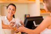 Baker giving cookies to customer — Stock Photo
