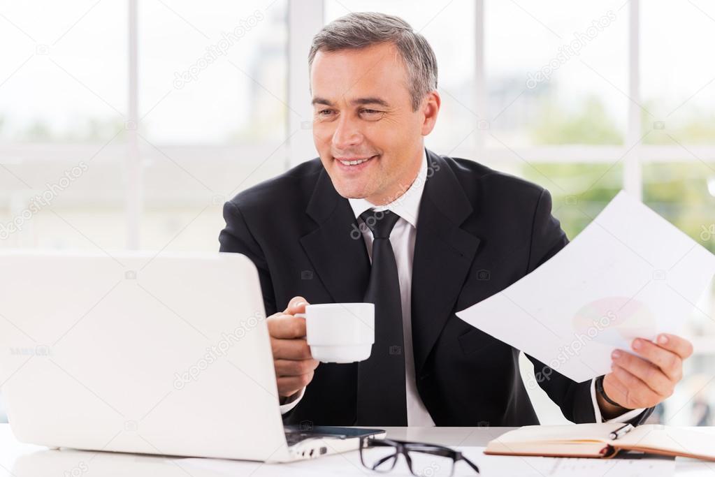 成熟的男人工作和喝咖啡