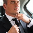 Mature businessman adjusting necktie in car — Stock Photo #52888763