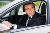 Mature businessman driving car — Stock Photo