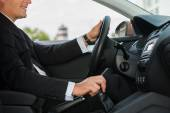 Driving with comfort. Close-up of cheerful mature man in formalwear driving car and smiling — Stock Photo