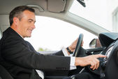 Mature man in formalwear driving car — Stock Photo