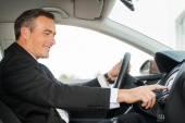 Mature man in formalwear driving car — Stock Photo